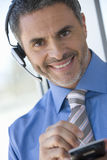 Businessman with hands-free telephone headset and electronic organizer Stock Photo