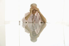 Businessman With Hands On Head At Conference Table. Stressed out senior businessman with hands on head sitting at conference table Royalty Free Stock Photo