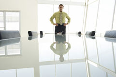 Businessman With Hands On Hips At Conference Table Stock Image