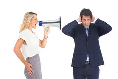 Businessman with hands on his ears because of megaphone Stock Images