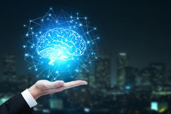 Artificial intelligence and innovation concept. Businessman hands holding abstract polygonal brain on blurry night city background. Artificial intelligence and Royalty Free Stock Image