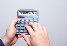 Businessman hands holding Calculator with Business Loan sign tex Stock Photos