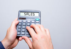Businessman hands holding Calculator with SALES sign text messag Royalty Free Stock Image
