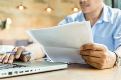 Businessman hands holding document paperwork and pen working on laptop. royalty free stock photo