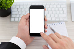 Businessman hands holding phone with isolated screen in the offi. Businessman hands holding phone with isolated screen on the desk in the office Stock Image