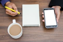 Businessman hands holding phone and writing on blank paper noteb. Ook by yellow pen and cup of coffee on wooden table in the office Royalty Free Stock Image