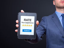 Businessman hands holding tablet with Rate your experience. Business concept. Isolated on black. Stock photo royalty free stock image