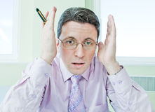 Businessman with hands near face in stress Stock Photos
