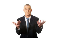 Businessman with hands open in undecided gesture Royalty Free Stock Photos