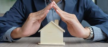 hands over wooden House model royalty free stock photography