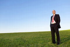 Businessman With Hands In Pockets On Grassy Field Against Sky Royalty Free Stock Photo