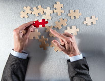 Businessman hands pointing a different jigsaw piece from puzzle group Stock Photos