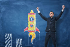 Businessman with hands raised in victory and rocket drawn in chalk on blue blackboard background Stock Photo
