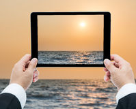 Businessman hands tablet taking pictures beach and sea Stock Image