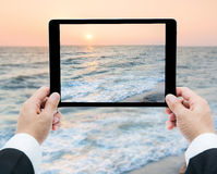 Businessman hands tablet taking pictures beach and sea Stock Photo
