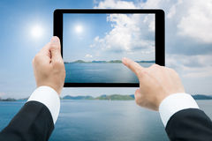 Businessman hands tablet taking pictures beach and sea Stock Images