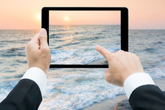 Businessman hands tablet taking pictures beach and sea Royalty Free Stock Photo