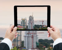 Businessman hands tablet taking pictures buildings under constru Stock Photography