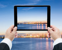 Businessman hands tablet taking pictures Commercial docks at sun Royalty Free Stock Photo