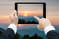 Businessman hands tablet taking pictures Majestic sunset in the Royalty Free Stock Photos