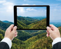 Businessman hands tablet taking pictures Mountains and blue sky Royalty Free Stock Photography
