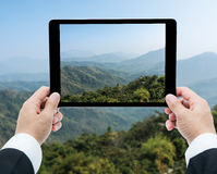 Businessman hands tablet taking pictures Mountains and blue sky Stock Photo