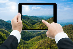 Businessman hands tablet taking pictures Mountains and blue sky Royalty Free Stock Images