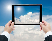 Businessman hands tablet taking pictures The sun and white cloud Royalty Free Stock Photography