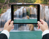 Businessman hands tablet taking pictures Waterfall deep forest Royalty Free Stock Photography