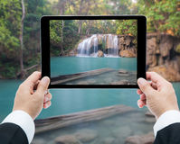 Businessman hands tablet taking pictures Waterfall deep forest Stock Photo