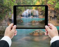 Businessman hands tablet taking pictures Waterfall deep forest Stock Images