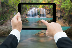Businessman hands tablet taking pictures Waterfall deep forest Royalty Free Stock Photos