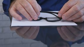 Businessman Hands Taking Eyeglasses from the Table to Read a Document stock images