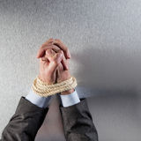 Businessman hands tied with rope praying for employee peace Stock Photography