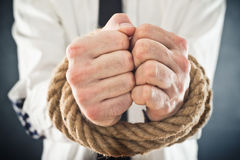 Businessman with hands tied in ropes. Business problems and difficulties, obstructions and limits in work Royalty Free Stock Photography