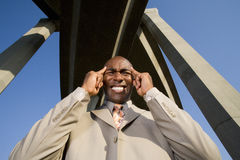 Businessman with hands to head beneath overpasses, low angle view Stock Photography