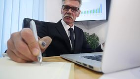 Businessman hands typing on laptop computer on wooden table and make some notes.  stock video