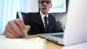 Businessman hands typing on laptop computer on wooden table and make some notes.  stock footage
