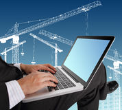 Businessman hands typing on laptop keyboard  with crane illustra Royalty Free Stock Photography