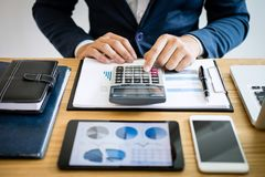 Businessman hands using text information on digital tablet to analyze financial statistical chart data and calculate cost of royalty free stock photo