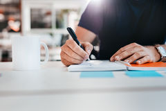 Businessman hands writing notes. Cropped shot of man writing on notepad. Hand of businessman taking notes while sitting at his desk in office Royalty Free Stock Photo