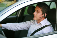 Businessman with handsfree bluetooth in car. Businessman in car with hands-free blue-tooth royalty free stock images