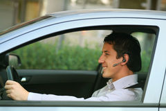 Businessman with handsfree bluetooth in car. Smiling businessman in car with blue-tooth hands-free royalty free stock photography