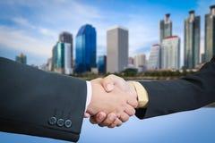 Businessman handshake with building area Stock Image