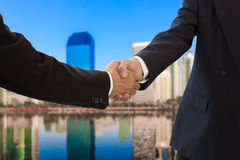 Businessman handshake with building background Stock Photography