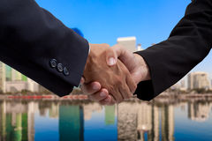 Businessman handshake with building background Stock Images