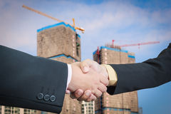 Businessman handshake with building construction Stock Photos