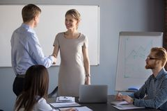 Businessman handshake business coach thanking for office present. Businessman shaking hand of smiling millennial female presenter or speaker thanking her for stock photo