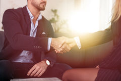 Businessman handshake with businesswoman in office in sunset Stock Photos