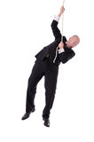 Businessman hanging on rope Stock Photos